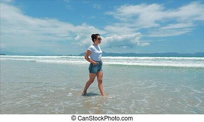 On a Tropical Beach Beautiful Scene of a Woman Walking on Ocean Beach at Sunset. Close-Up of Women's Legs European Beautiful Brunette, Walking Along the Beach, Slow Motion.