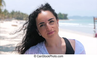 On a Tropical Beach Close-Up Portrait of European Beautiful Cute Brunette Young Woman or Cheerful Girl Looking in The Camera, Blowing Wind Hair the Wind , Slow Motion.