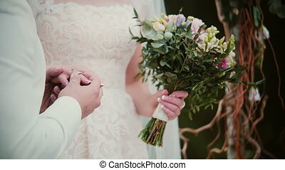 On a wedding day groom puts a golden ring on a bride finger. Close-up exchanging wedding rings