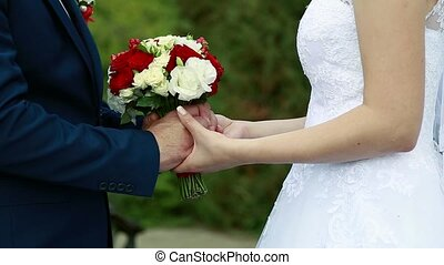 On a wedding day the groom strokes the bride's hand, the wedding bouquet