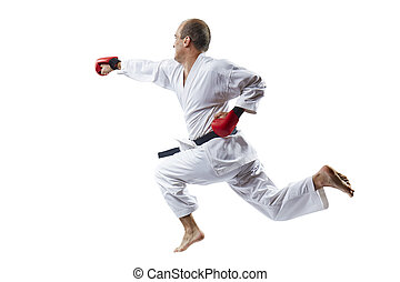 On a white background an athlete with red overlays on his hands beats with a hand in a jump