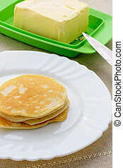 On a white plate stack of pancakes