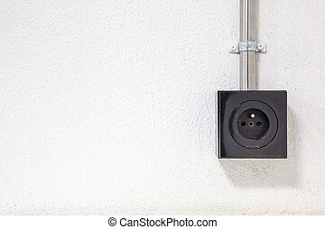 outlet in black - on a white wall, there is a socket with...