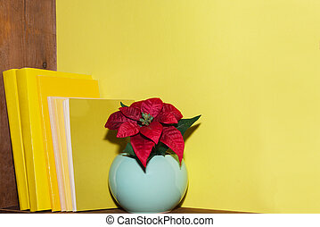 On a wooden shelf are books with yellow covers and a red flower in a blue flowerpot. Yellow interior