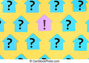 On a yellow background are glued blue stickers with question marks written on them. In the center on the lilac sticker is an exclamation mark. Bright layout.