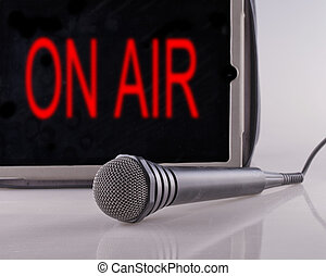 """On Air - Microphone with a tablet with the words """"on air"""""""