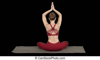 Young sporty woman sitting in lotus pose, join hands above...