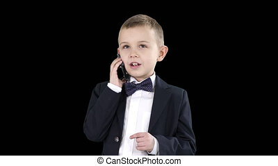 Cute little boy talking on his smartphone and standing in a dark suit, Alpha Channel