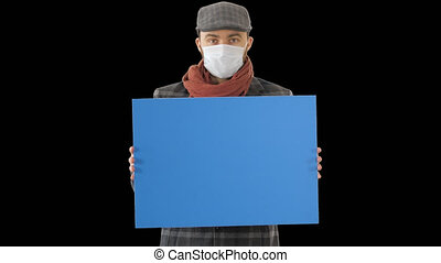 On Alpha Matte. Close up. Mockup blue screen. Man in a trendy outfit and medical mask holding blank placard, Alpha Channel. Professional shot in 4K resolution. 53. You can use it e.g. in your medical, commercial video, business, presentation, broadcast