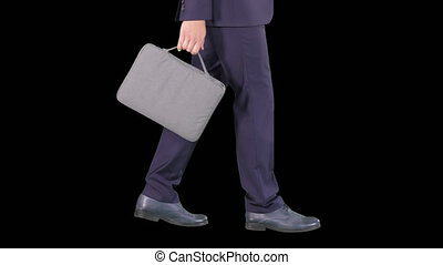 Handsome businessman in a suit walks with a briefcase, Alpha Channel