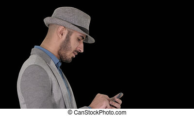 On Alpha Matte. Close up. Side view. Serious arabic casual man using smartphone while walking, Alpha Channel. Professional shot in 4K resolution. 011. You can use it e.g. in your commercial video, business, presentation, broadcast