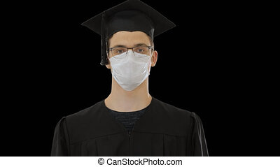 Young man with graduation gown in medical mask, Alpha ...