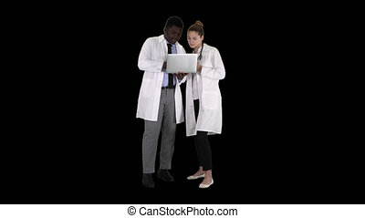 Medical staff working in front of a grey laptop while standing, Alpha Channel