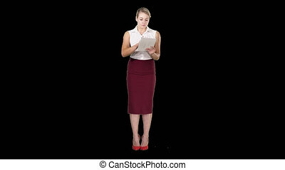 Attractive businesswoman using a digital tablet while standing, Alpha Channel