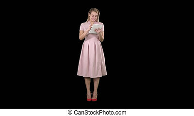 Pretty young woman in pink dress holding tablet and looking...