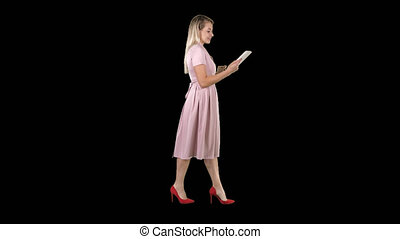 Blonde in pink dress walking and using tablet, Alpha Channel...