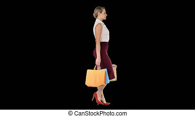 Happy full length woman holding paper shopping bags in every...
