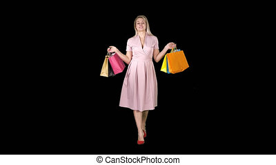 Young blonde girl in pink dress showing to camera shopping...