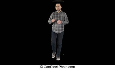 Young confident man in shirt and jeans walking towards...