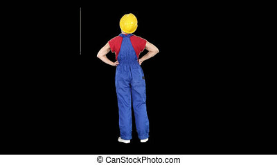 Woman engineer in construction helmet stands with hands on...