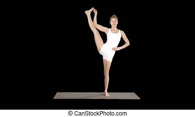 Beautiful smiling happy young woman doing yoga exercise on mat, standing in Vrksasana Posture, Tree Pose, Alpha Channel