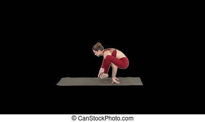 Beautiful woman practices handstand yoga asana Tittibhasana...