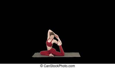 Beautiful young woman wearing red sportswear doing yoga or pilates exercise One Legged King Pigeon pose, Eka Pada Rajakapotasana, Alpha Channel