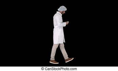 Arabic doctor walking and putting medical cap on, Alpha...