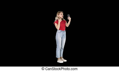 Blonde woman preening in front of the smartphone, Alpha...