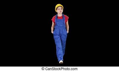 Woman builder with hands in pockets walking and telling a...