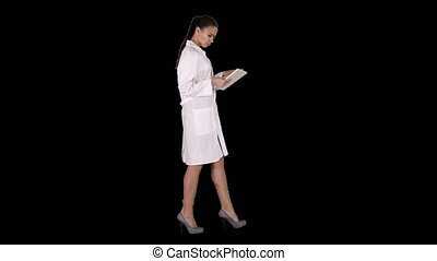 On Alpha Matte. Full length side view. Woman doctor using tablet pc and walking, Alpha Channel. Professional shot in 4K resolution. 013. You can use it e.g. in your commercial video, business, presentation, broadcast