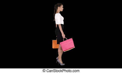 Young woman with shopping bags walking out from shop, Alpha Channel