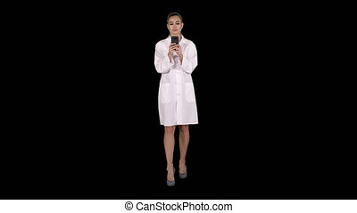 Cheerful cute young woman doctor typing text on phone while...