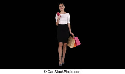 Happy young woman with smartphone making picture of her shopping bags, Alpha Channel