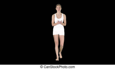 Woman in white sport clothes holding a paper cup of coffee and talking to camera, Alpha Channel
