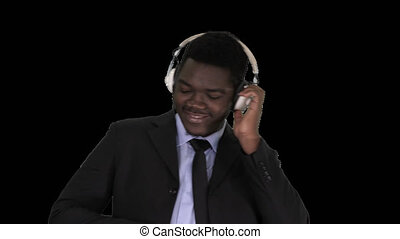 Black businessman dancing to music in headphones, Alpha Channel