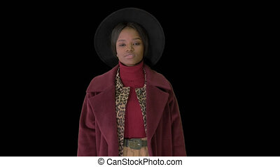 On Alpha Matte. Medium shot. Cute afro model in coat touching hat walking, Alpha Channel. Professional shot in 4K resolution. 4151. You can use it e.g. in your commercial video, business, presentation, broadcast