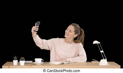 Beautiful woman taking a selfie with her cell phone sitting at the desk, Alpha Channel