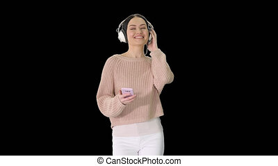Happy girl walking listening to music with smart phone wearing headphones, Alpha Channel