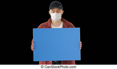 On Alpha Matte. Medium shot. Mockup blue screen. Mature Male Farmer In Medical Mask Holding Blank Placard, Alpha Channel. Professional shot in 4K resolution. 53. You can use it e.g. in your medical, commercial video, business, presentation, broadcast