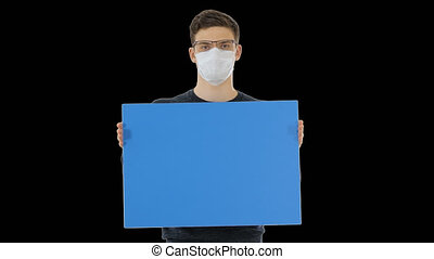 On Alpha Matte. Medium shot. Mockup blue screen. Young man in medical mask showing and displaying placard, Alpha Channel. Professional shot in 4K resolution. 53. You can use it e.g. in your medical, commercial video, business, presentation, broadcast