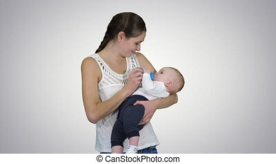On Alpha Matte. Medium shot. Mother gives baby to drink from bottle, Alpha Channel. Professional shot in 4K resolution. 019. You can use it e.g. in your commercial video, business, presentation, broadcast