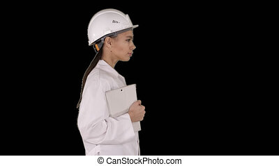 Attractive Hispanic woman in white lab coat and white safety hard hat walking holding notebook or tablet, Alpha Channel