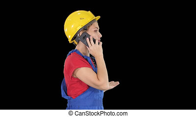 Beautiful young builder woman wear a yellow safety helmet making a call, Alpha Channel