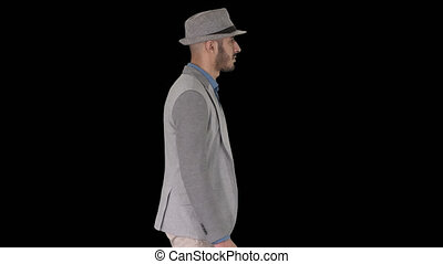 On Alpha Matte. Medium shot. Side view. Casual arabic man in hat walking, Alpha Channel. Professional shot in 4K resolution. 011. You can use it e.g. in your commercial video, business, presentation, broadcast