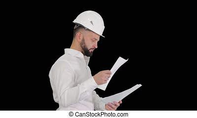 Male engineer walking in a hard hat looking at documents, ...