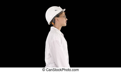 On Alpha Matte. Medium shot. Side view. Scientist physicist woman walking in lab coat and hardhat, Alpha Channel Professional shot in 4K resolution. 006. You can use it e.g. in your commercial video, business, presentation, broadcast