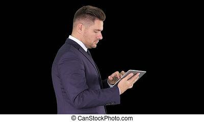 Smart senior businessman using a technology tablet, Alpha...