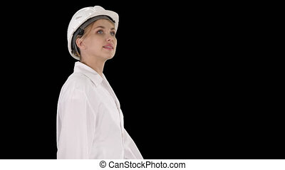 Young woman in hard hat walking and looking around, Alpha ...