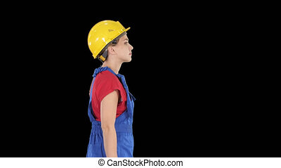 Young woman in yellow hardhat walking, Alpha Channel - On...